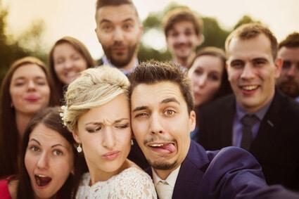 הכלה והחתן עושים תמונת סלפי עם האורחים